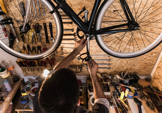 Young mechanic working on bike maintenance in his rustic workshop.