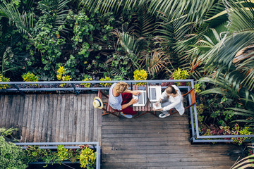 Man and Woman Working on Vacation in a Tropical Area
