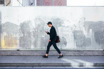Stylish asian businessman using phone walking on the street.