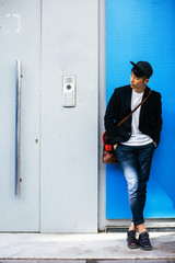 Stylish asian businessman waiting on the street.