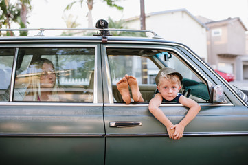 Cute kids hanging out in car and peeking out the window of an old car