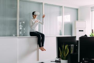 Woman wearing virtual reality headset sitting in office