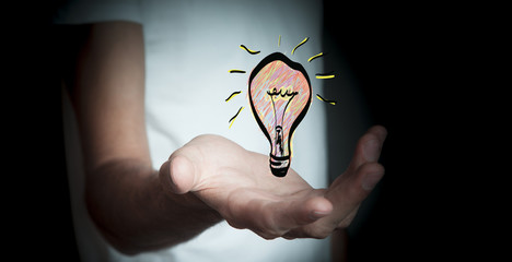 Businessman holding hand drawn lightbulb in his hand
