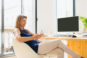 Relaxed mature woman using a phone taking a break at work.