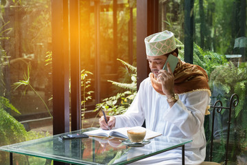 arab muslim man use smart phone and write on book in coffee shop ,freelance no working space lifestyle.