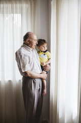 Grandfather with his grandson looking outside of a window