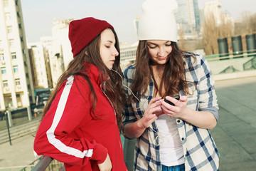 Две девушки слушают музыку в наушниках