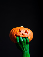 Green hands of a man holding a pumpkin halloween. Halloween theme