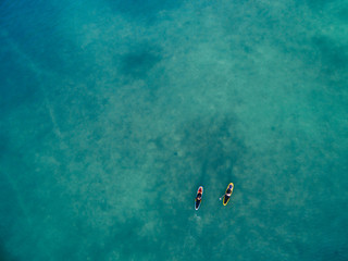 Aerial drone image of two women stand up paddleboarding in the o