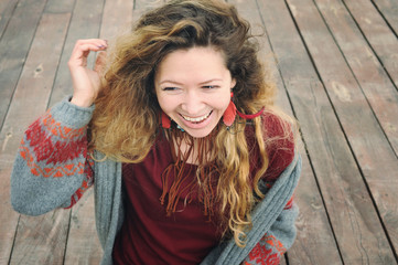 Happy smiling young woman portrait dressed in gray knitted jersey