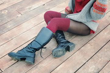 Female legs dressed in knee high boots and knitted stockings, woman sitting on a wooden planking