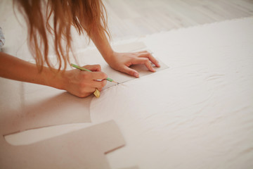 girl making a pattern sketch with a pencil and a template