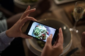 Woman taking photo of meal with mobile phone