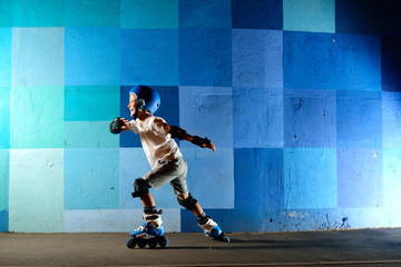 Cute little boy on roller skates running against the blue graffiti wall