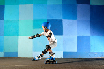 Young boy on roller skates making slide against the blue graffiti wall