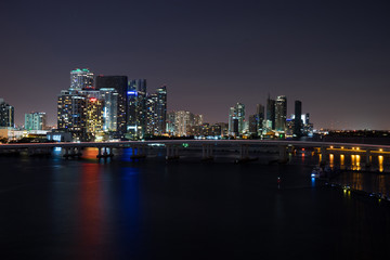Miami at night. View from atop a glowing building with a bridge