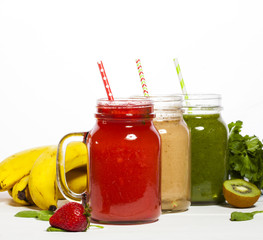 Assortment of fruit and vegetable smoothies in glass jars with straws