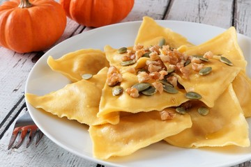 Pumpkin filled ravioli pasta with nuts, pumpkin seeds and olive oil, close up on a white plate