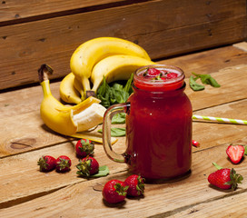 Strawberry and banana smoothie or milkshake in a jar on wooden background.