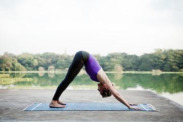 Woman doing yoga at a lake