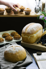 Fresh bread on table, woman places muffins to cool on window sill