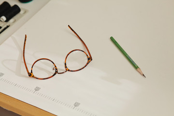Vintage glasses and pencil lie on the sewing machine