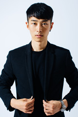 Portrait of an attractive asian man wearing a black suit.
