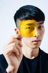 Young man looking through transparent yellow square