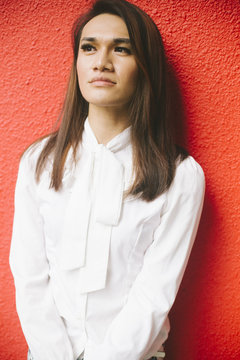 Portrait of woman in white blouse against red wall