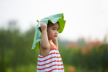lovely little girl playing with lotus leaf outdoor