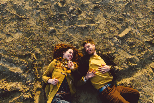 Young couple looking to each other laying on the sand