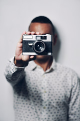 Man holding old camera while standing against white background