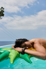 Relaxed brunette sunbathing on inflatable in pool