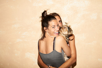 Cheerful brunette with friend and dog smiling back at camera