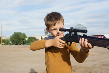 boy aims bb gun at target