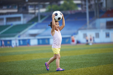 little girl playing football outdoor in the football field
