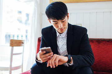Portrait of a young businessman watching his smart watch sitting in a coffee bar.