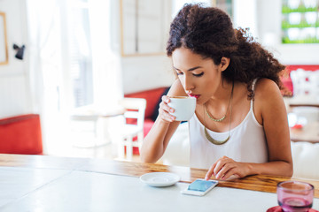 Young businesswoman using phone whilst having breakfast in a coffee bar.