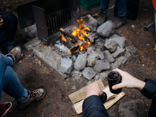 Young man holding coffee mug near campfire while camping
