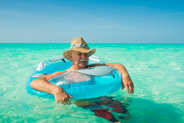 Old Man Tourist at Sunny Turquoise White Sand All Inclusive Resort Beach In Caribbean