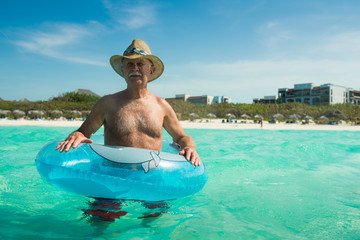 Old Man Tourist at Sunny Turquoise White Sand All Inclusive Resort Beach In Cuba Caribbean