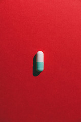 Bicolor capsule on red background from above.