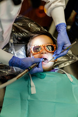 Asian kid getting a filling on his teeth at a dentist office