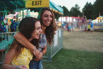 Two friends walking through a carnival