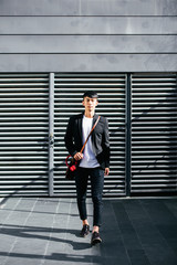 Young asian businessman walking on the street.