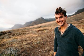 Handsome brunet with windy hair smiling at camera against of landscape