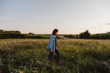 Woman walking through field of tall grass