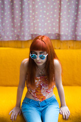 Portrait of ginger girl with sunglasses sitting on orange bed