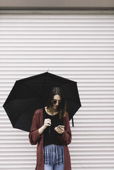 portrait of real young woman using her smartphone on the street in a rainy day.