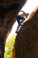 Young woman rock climbing a narrow crack